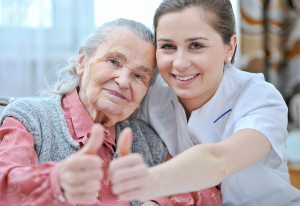 caregiver and elderly woman showing their thumbs-up