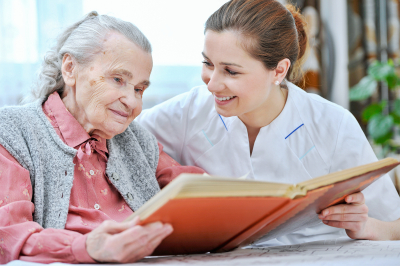 caregiver and elderly woman looking at the album
