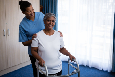 caregiver and elderly woman standing